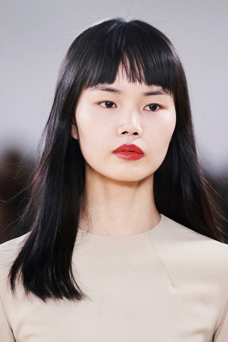 capelli lunghi scalati con frangia donna asiatica con rossetto rosso