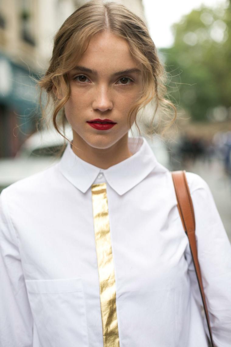 frangia lunga scalata ai lati ragazza con capelli biondi mossi camicia bianca