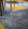 quadrotte di moquette di colore grigio e giallo salotto con mobili di legno