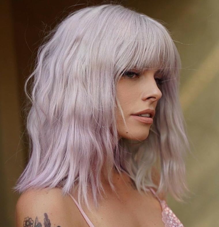 ragazza con tatuaggio sul braccio taglio capelli con frangia scalata colorazione rosa