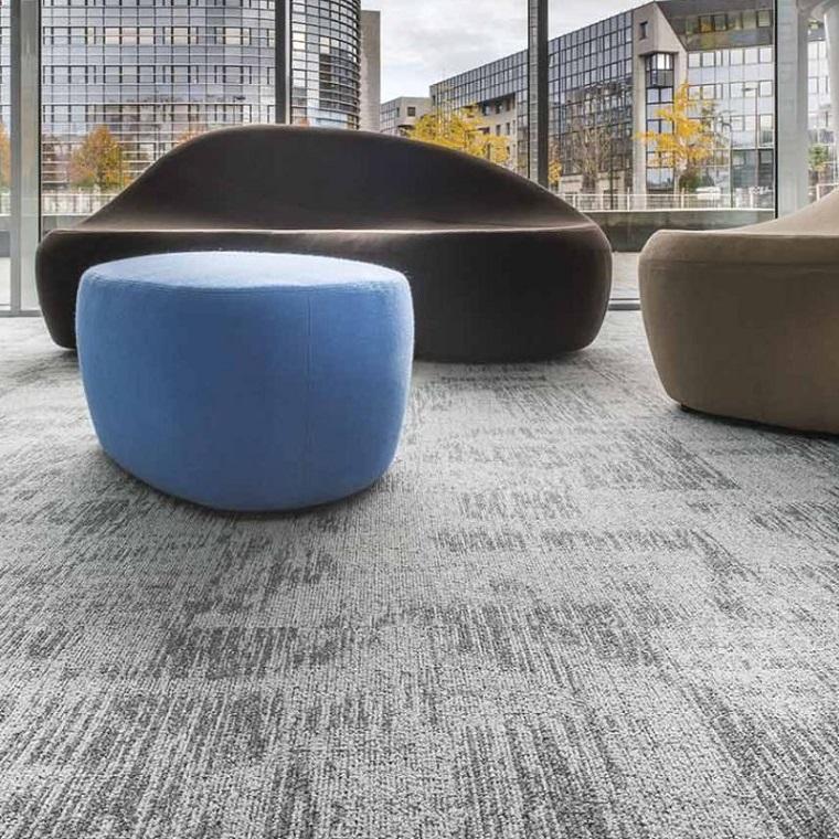 soggiorno con divano marrone pavimentazione con quadrotte di moquette