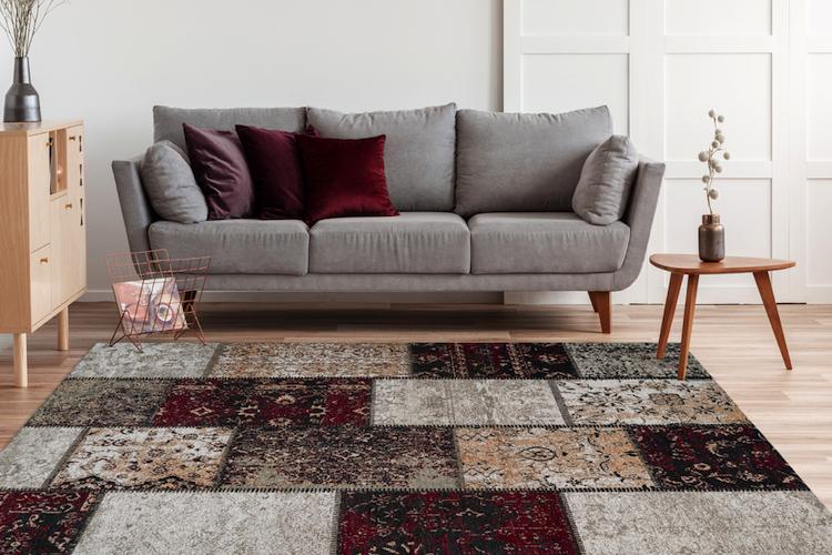 soggiorno in legno tappeto in stile scandinavo grigio divano con cuscini decorativi fantasia