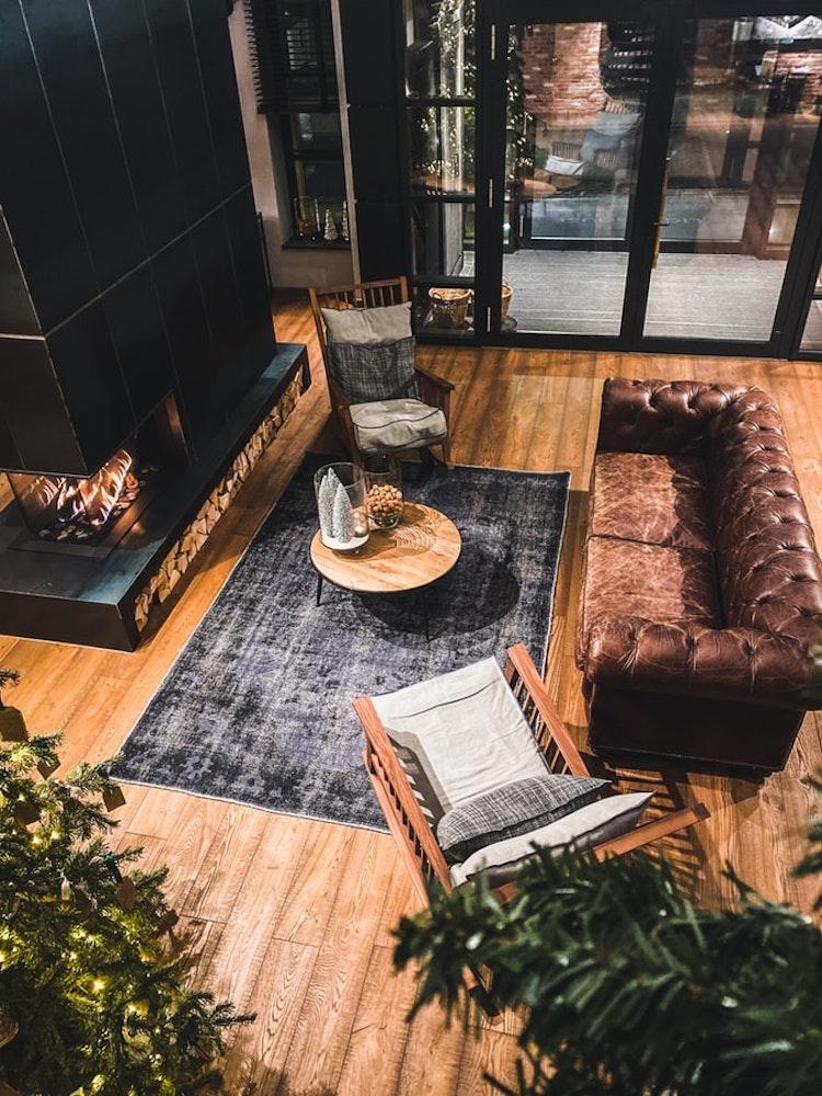 soggiorno in stile classico con divani pavimento in legno chesterfield con moquette grigia