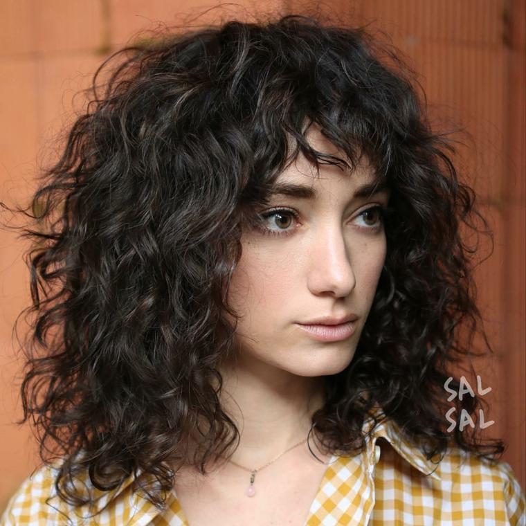 taglio capelli medi ricci ragazza con frangia aperta riccioli camicia gialla a quadretti