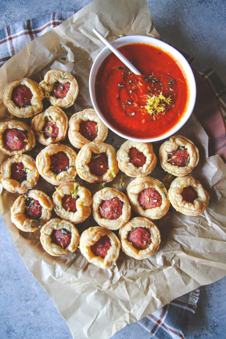 antipasti veloci ed economici stuzzichini di wustel avvolti in pasta sfoglia ciotola con salsa di pomodoro
