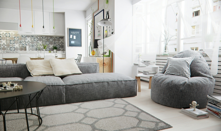 casa stile nordico open space cucina e soggiorno divano poltrona grigia