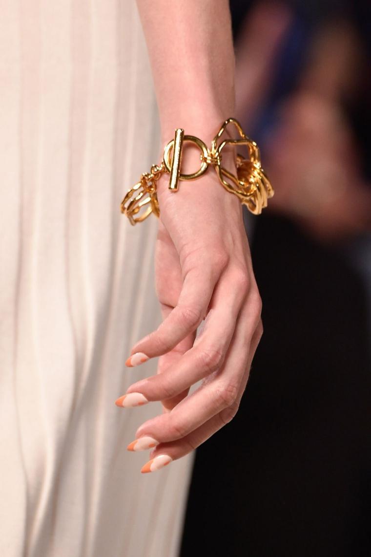 donna con braccialetto in oro manicure stiletto french arancione colori autunnali unghie