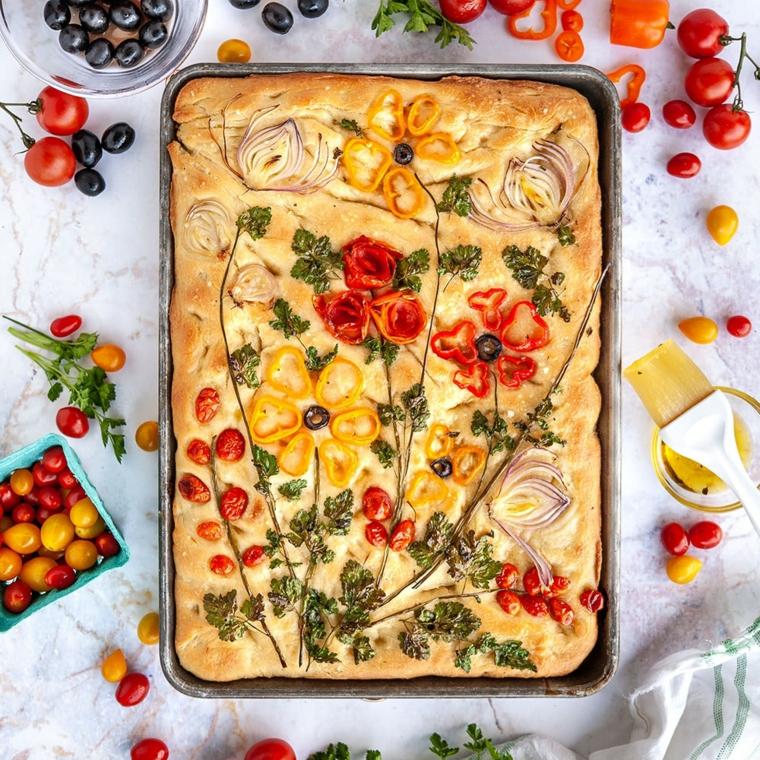 focaccia con verdure teglia con pizzia con disegni di peperoni e pomodorini