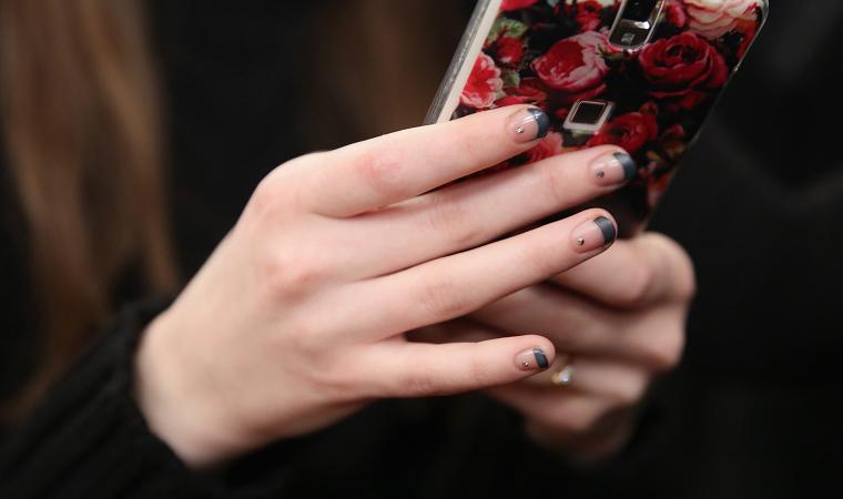 french manicure colore blu unghie corte ovali donna con telefono in mano