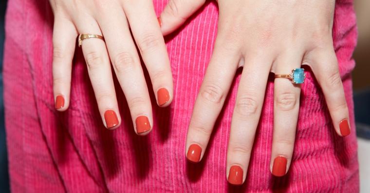 manicure corta con smalto gel rosso anello con diamante azzurro colori unghie inverno 2020