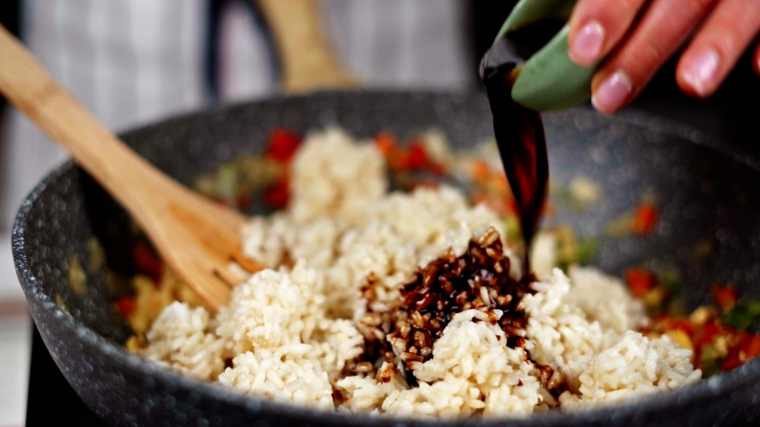 padella con riso fritto vegetariano aggiungere salsa di soia come condimento