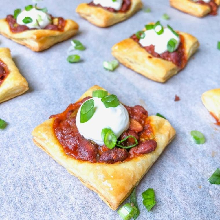 pizzette di pasta sfoglia salsa di pomodoro e ini mozzarelle cosparse con erba cipollina