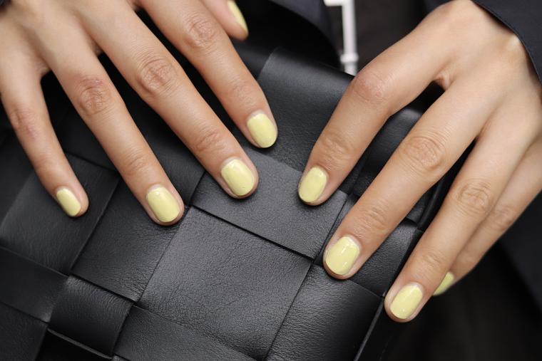 semipermanente unghie corte smalto gel giallo donna che tiene una borsetta in pelle nera