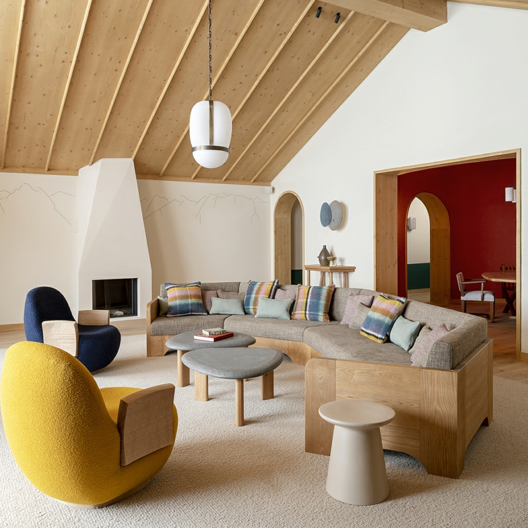 soggiorno con divano in legno soffitto in pendenza con travi poltrone colorate