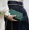 unghie invernali manicure corta con smalto di colore nero borsetta tracolla verde pelle effetto crocodillo