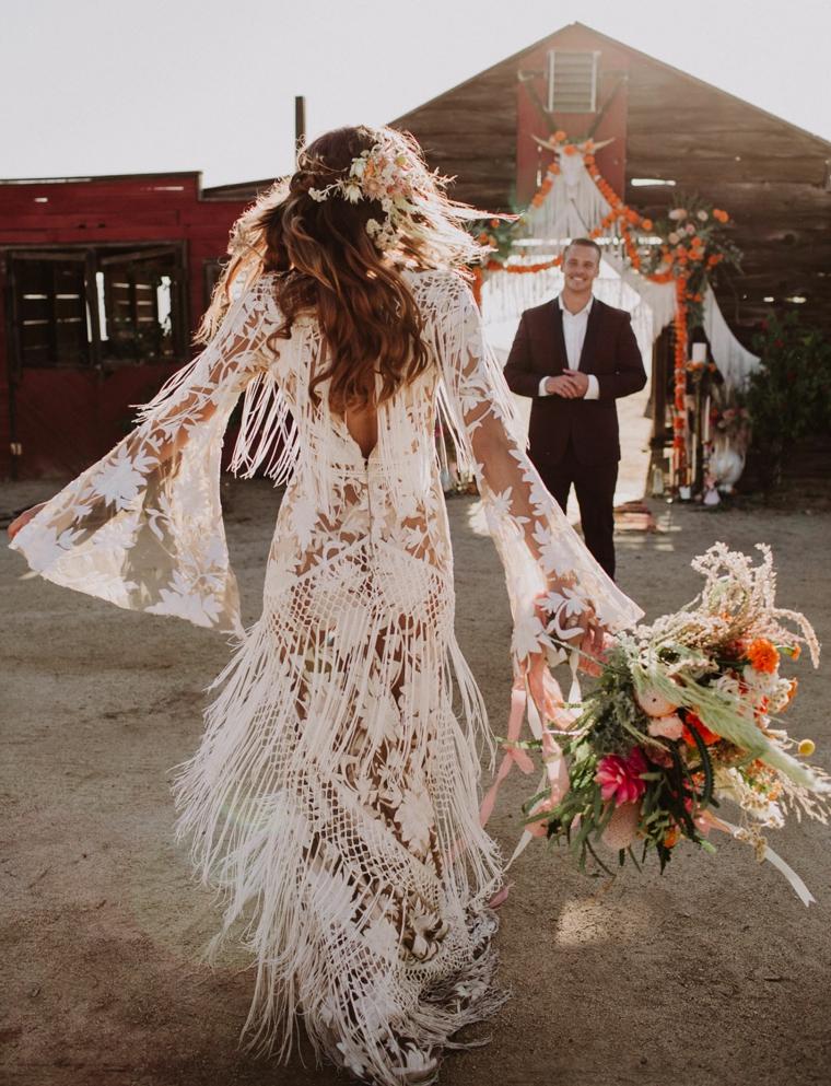 vestito da sposa stile boho chic con piume donna con bouquet di fiori in mano