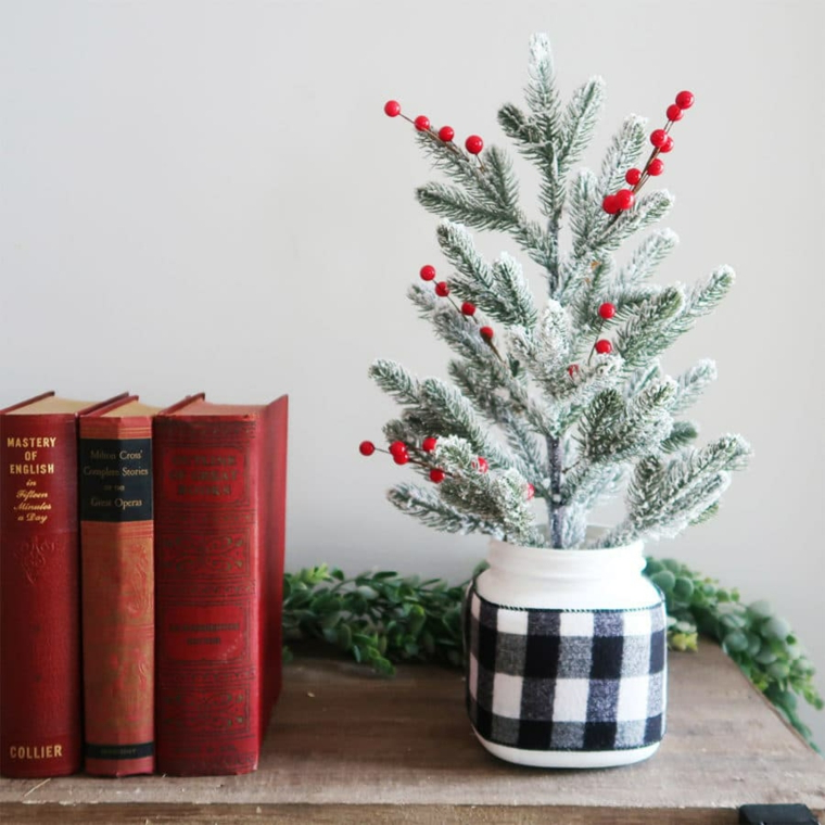 albero di natale bianco addobbato vaso con rametti decorati con bacche rosse