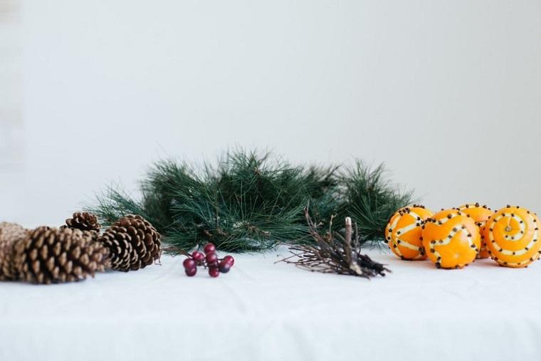 arance punzechiate con chiodi di garofano decorazione tavola natalizia con rametti e pigne