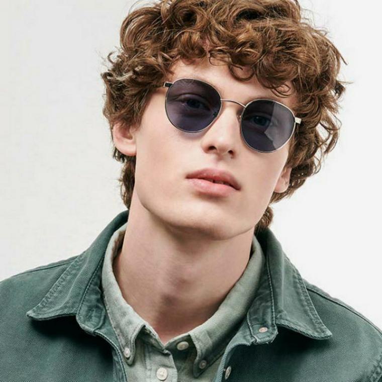 capelli mossi uomo ragazzo con chioma di colore castano occhiali da sole tondi