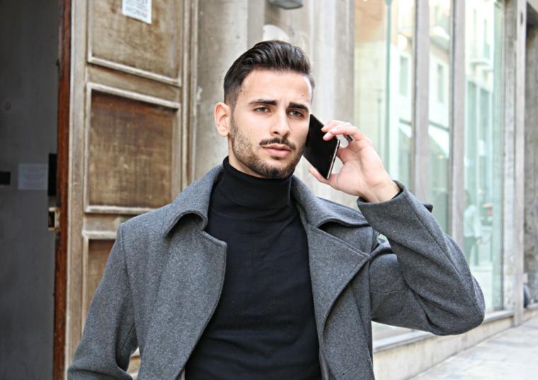 capelli rasati uomo ragazzo che parla al telefono uomo con ciuffo tirato indietro