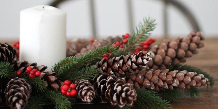 centrotavola con le pigne tavola con rametti bacche rosse e candela grande