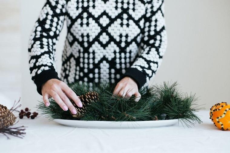 centrotavola natalizio con pigne arangiare un piatto con rametti verdi e arance