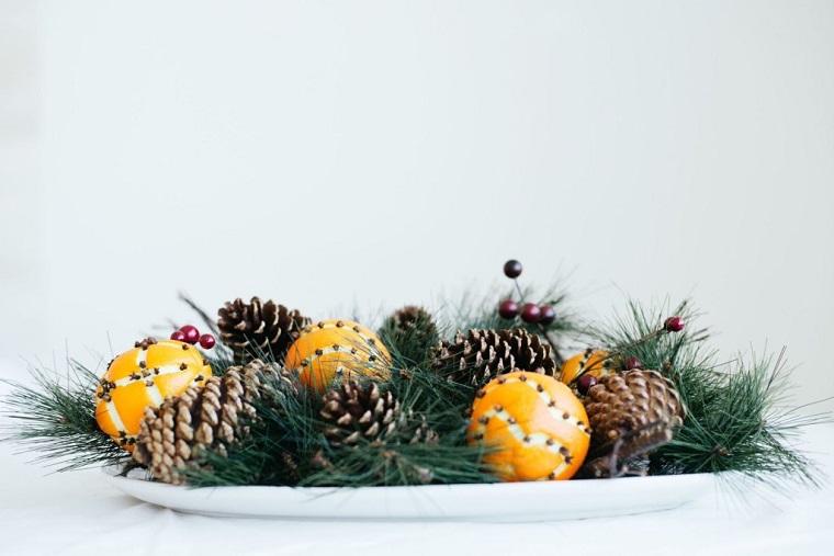 centrotavola natalizio con pigne piatto con rametti verdi e arance