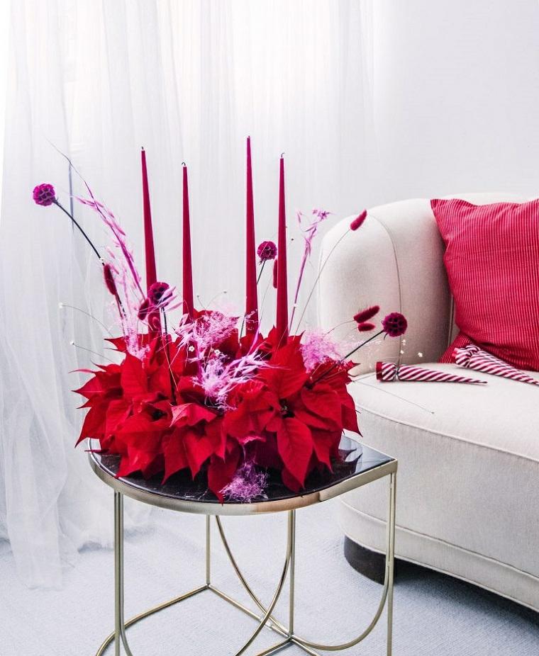 composizione natalizia con stelle di natale finte e candele rosse lunghe