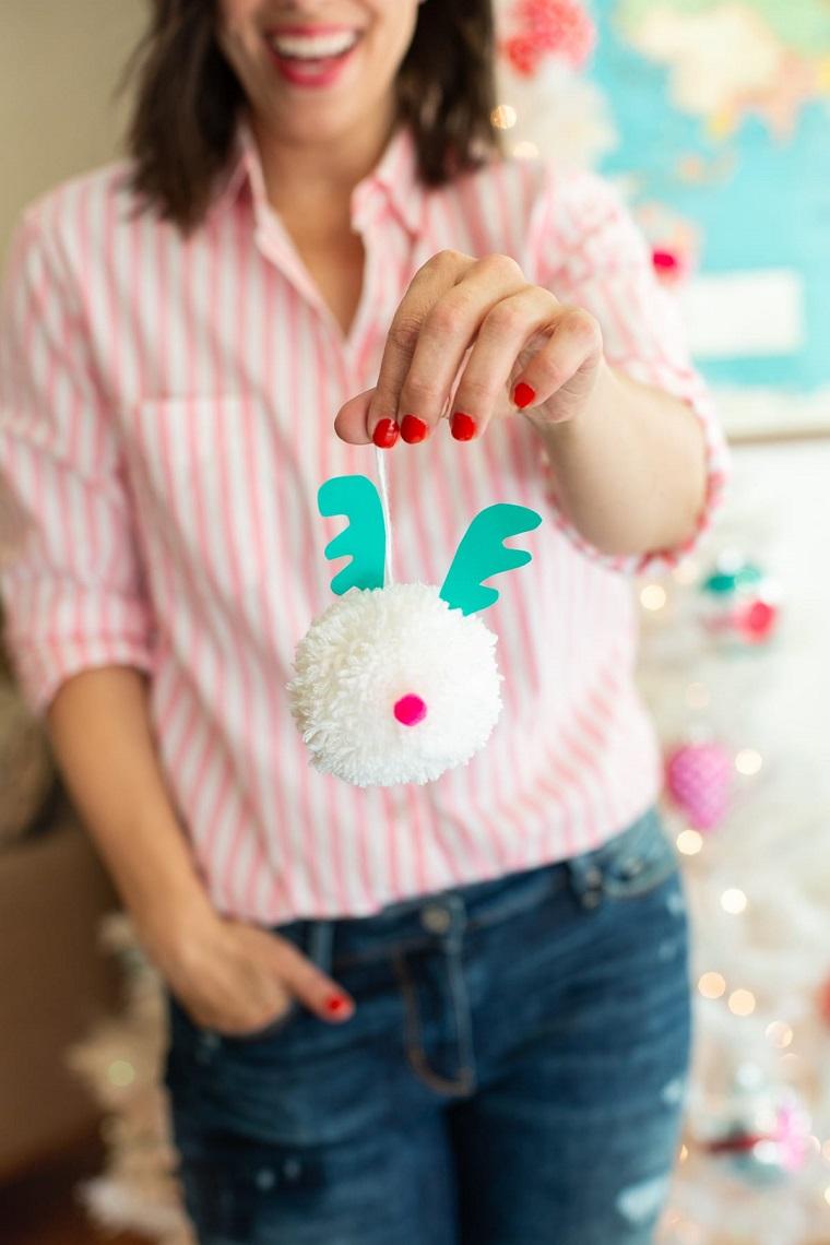 donna che tiene un pom pom di lana addobbi natalizi fatti a mano