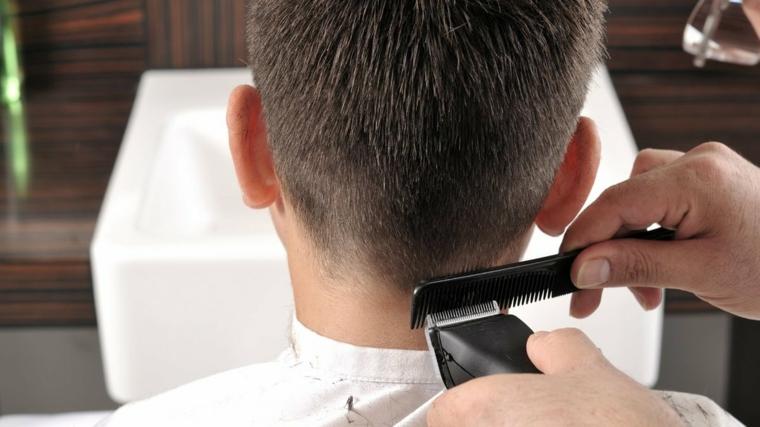 parrucchiere che taglia con tagliacapelli capelli sfumati uomo