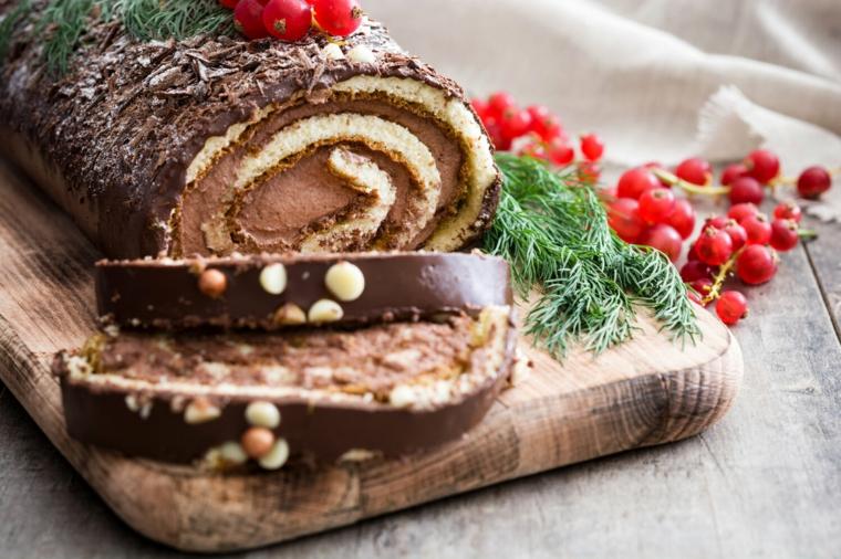 rotolo di cioccolato con mirtilli rossi decorazione dolce natalizio con rametti verdi