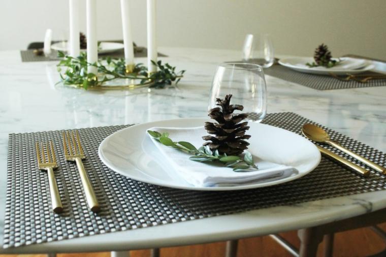 segnaposto natalizi con pigne tavola apparecchiata con piatti e tovagliolo di stoffa