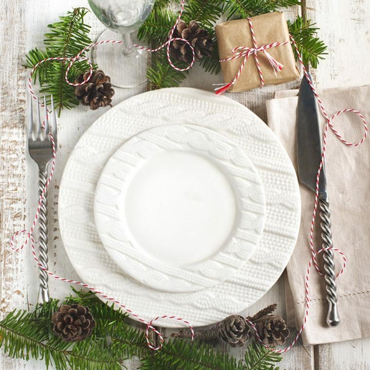 tavola apparecchiata per natale segnaposto con pacchettino regalo decorazione con rametti e pigne