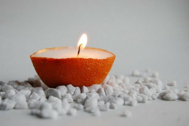 buccia di arancia utilizzata come candela di cera bianca con stoppino