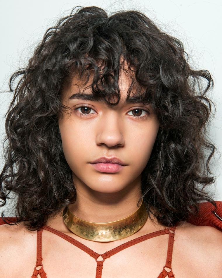 capelli ricci media lunghezza con frangia pettinatura donna colore castano