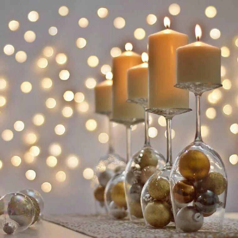centrotavola di natale con bicchieri di vetro e candele composizione con palline natalizie