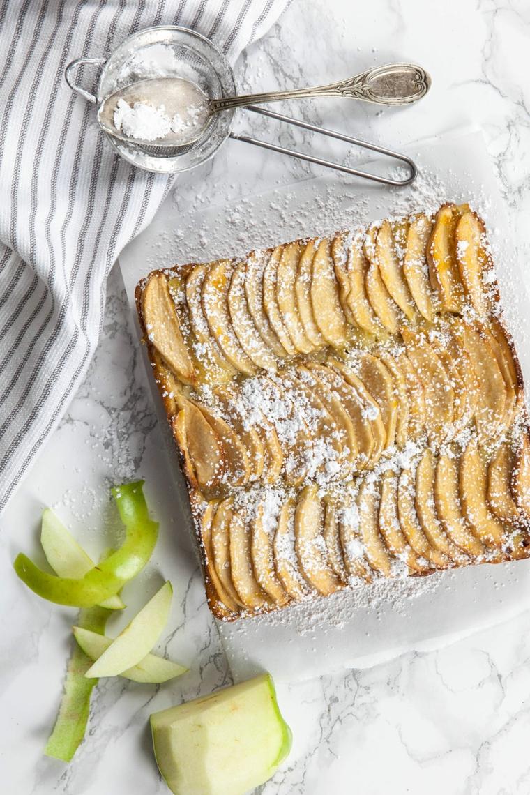 dolce ricoperto con zucchero a velo e fette di mela ingredienti per torta vegana