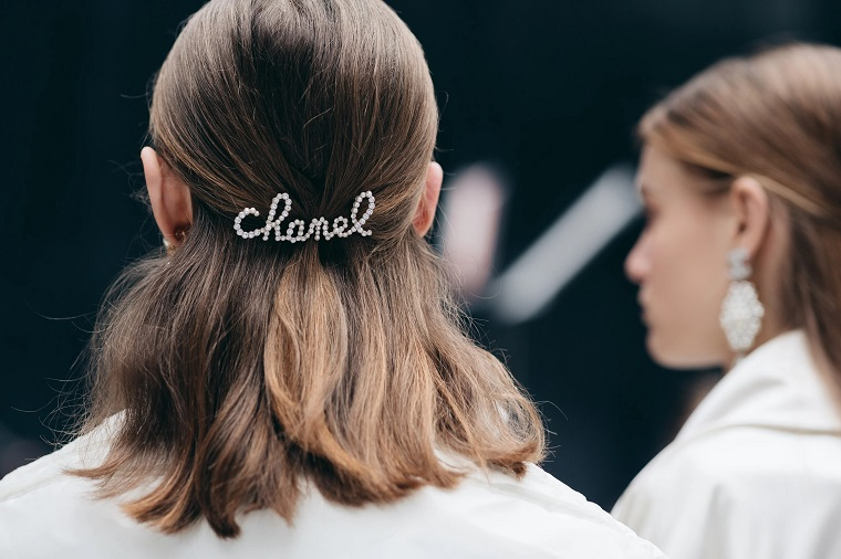 donna con capelli castani taglio caschetto lungo acconciatura semi raccolto con molletta chanel