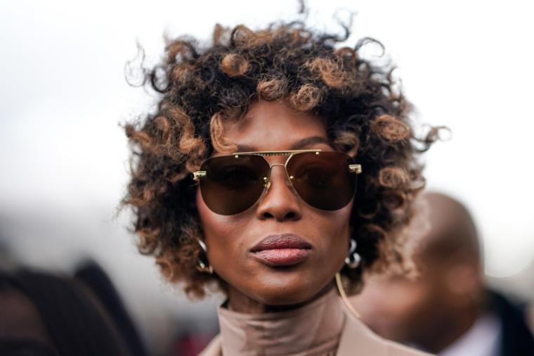 pettinatura capelli ricci colore castano bronde donna con occhiali da sole