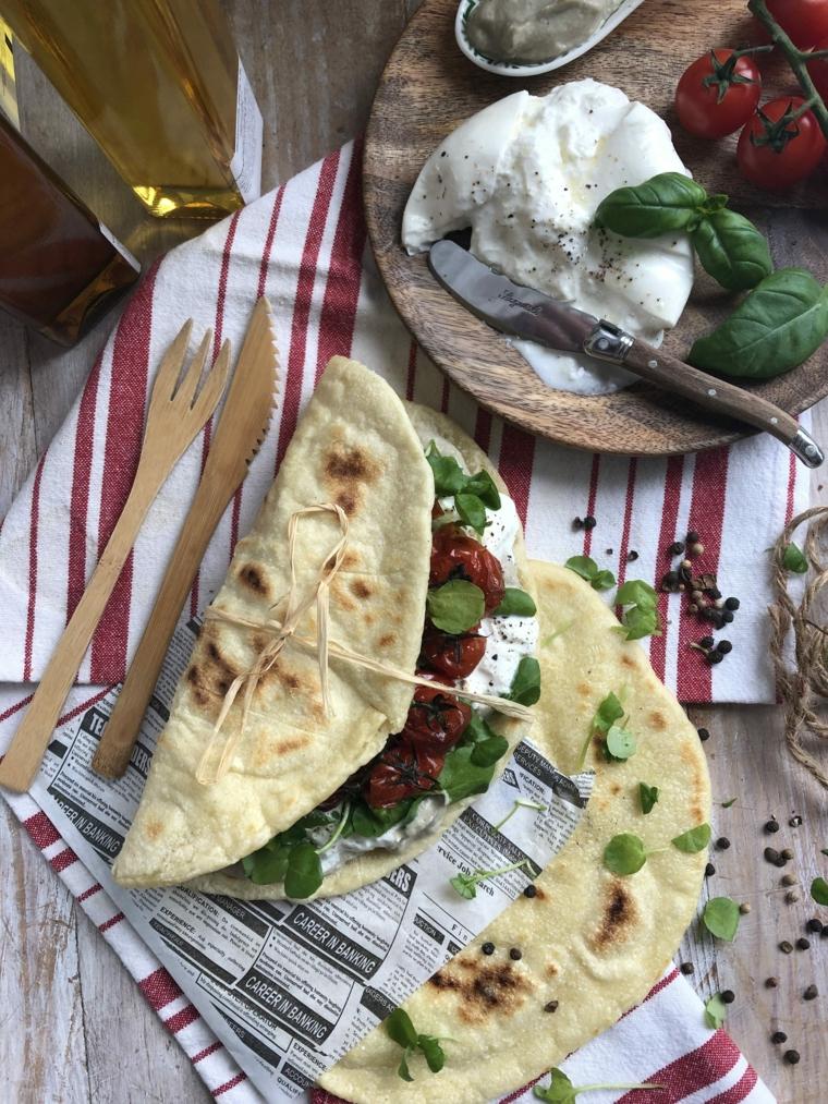 piada piegata farcita con pomodori secchi stracchino e foglie di basilico