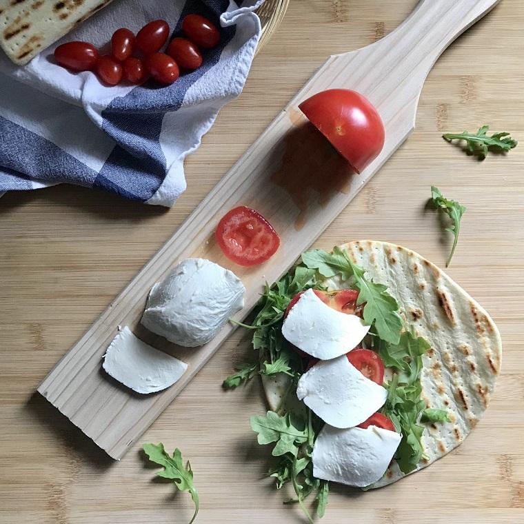 piadina ricetta veloce tagliere di legno con fette di pomodoro e mozzarella