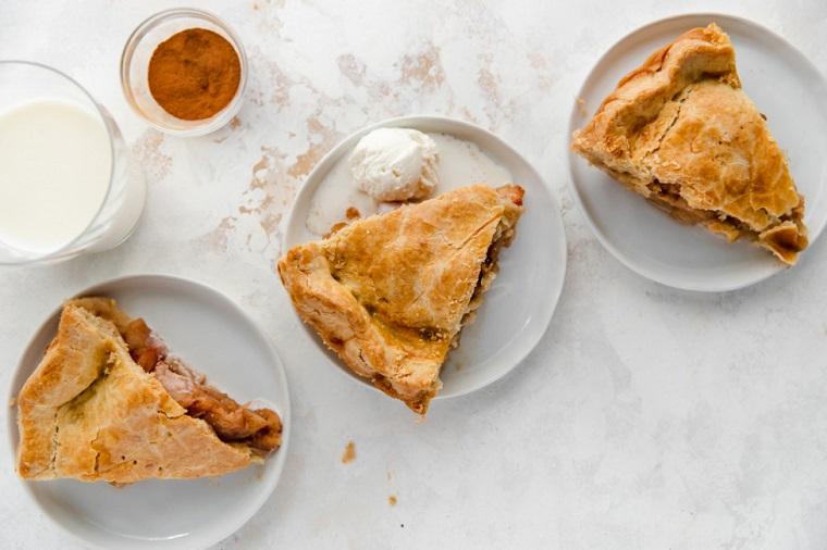 piattini con pezzi di torta di mele sofficissima ripieno cosparso di cannella