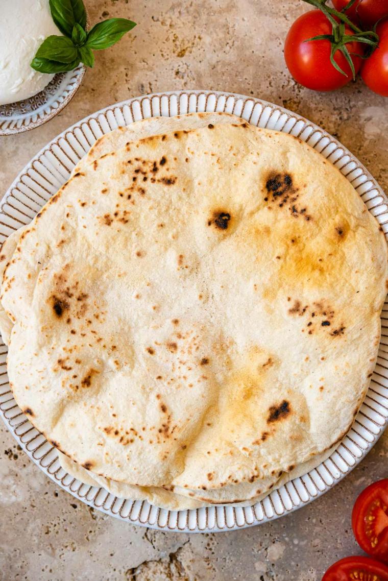 piatto con piada fatta in casa crescia da farcire con pomodoro e mozzarella