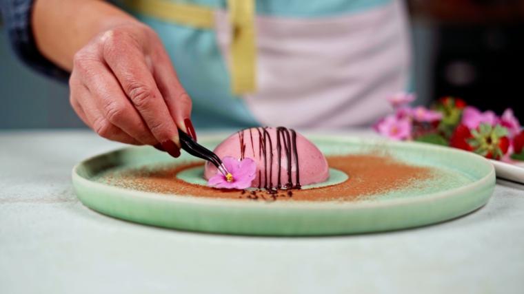 ricetta panna cotta ai lamponi decorazione con fiorellino piatto decorato con cacao in polvere