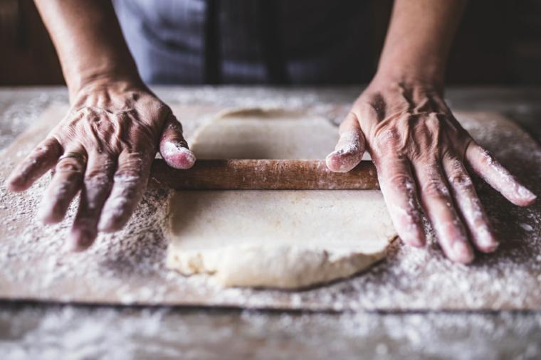 ricetta piadina senza strutto donna che stende impasto per pizza con mattarello
