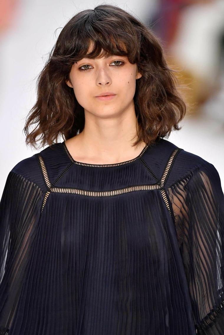 tagli di capelli mossi donna con camicia nera colorazione castano