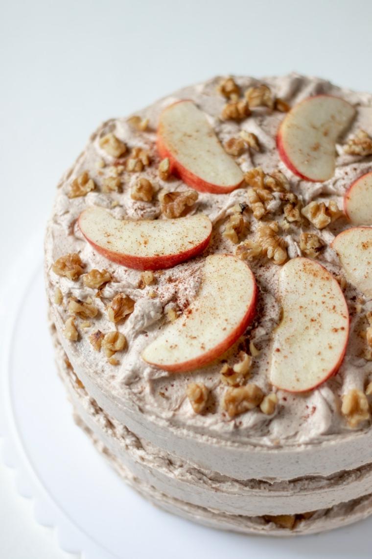 torta con tre strati ricoperti con panna dolce decorato con noci e fette di mele