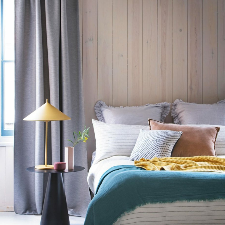 boiserie dietro letto zona notte con tende grigie comodino con lampada