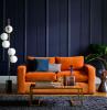 divano due posti di colore arancione pannelli boiserie in poliuretano tavolino in vetro con decorazioni