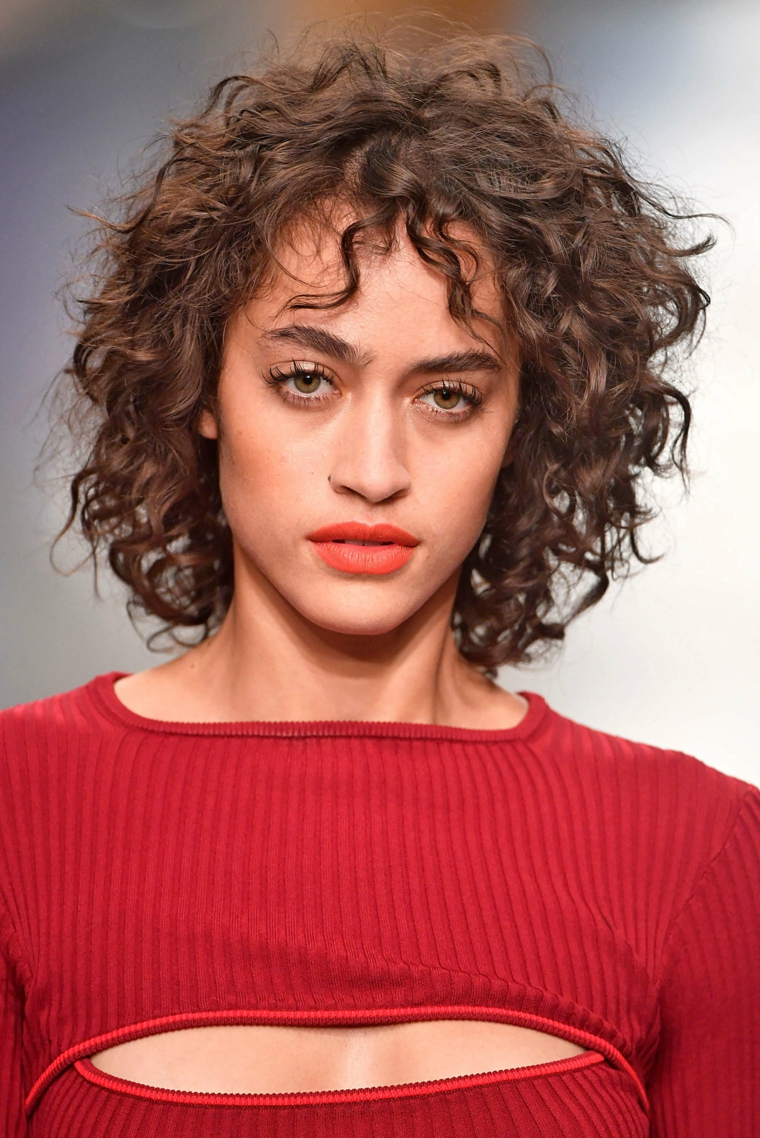 donna con acconciatura ricci tagli medio corti pratici capelli castani con frangia